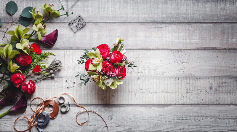 Ramo de rosas rojas, de corazones, de calas, de claveles y de cintas en la tabla foto de archivo libre de regalías