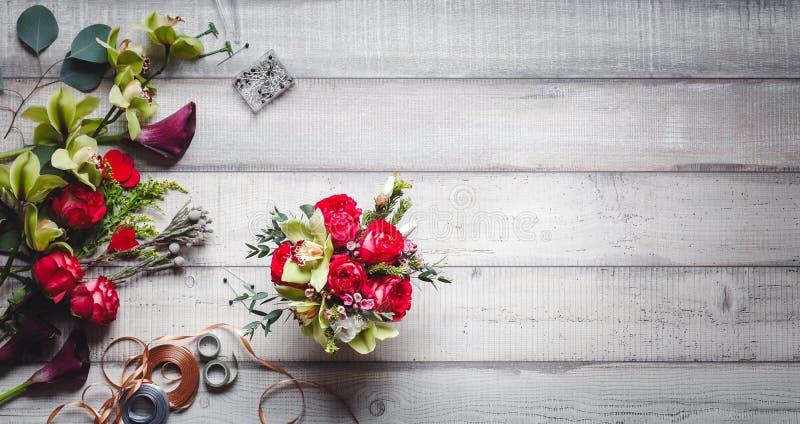 Ramo de rosas rojas, de corazones, de calas, de claveles y de cintas en la tabla fotografía de archivo libre de regalías