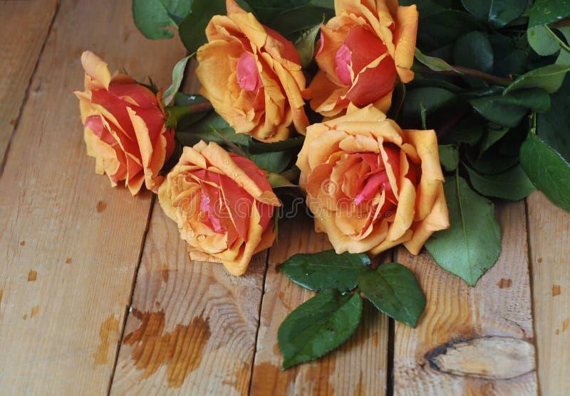 Ramo de rosas rojas frescas en fondo de los tableros de madera fotografía de archivo