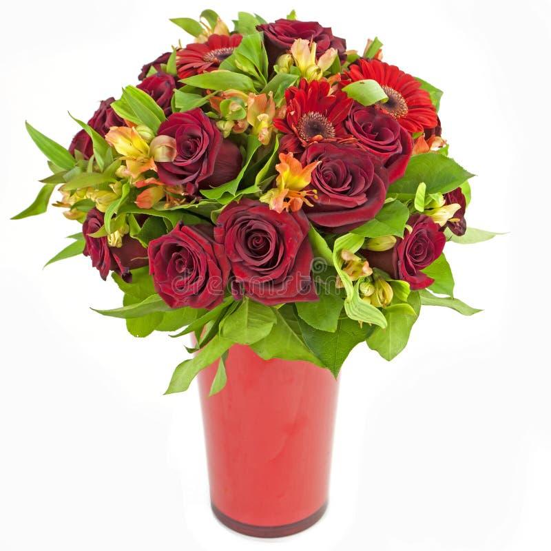 Ramo de rosas rojas y de gerberas en el florero aislado en blanco imagenes de archivo