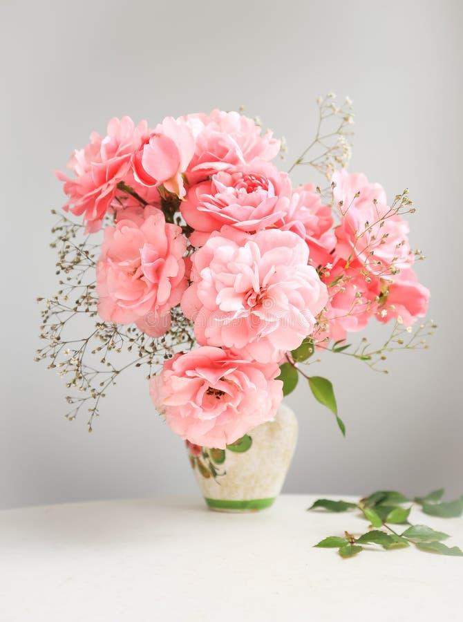 Ramo de rosas rosadas en un florero en un fondo gris imagen de archivo