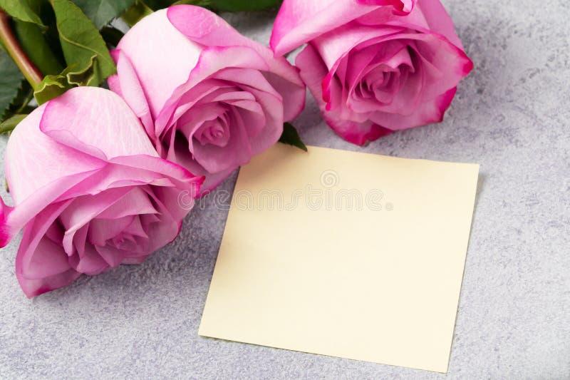 Ramo de rosas rosadas y una nota en blanco sobre la tabla imagen de archivo
