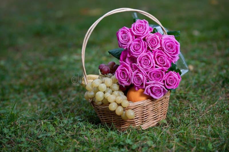 Ramo de rosas y de frutas rosadas en una cesta en una hierba fotos de archivo