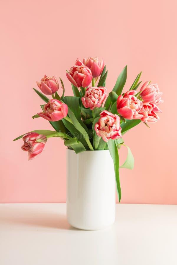 Ramo de tulipán rojo en florero en rosa milenario imágenes de archivo libres de regalías