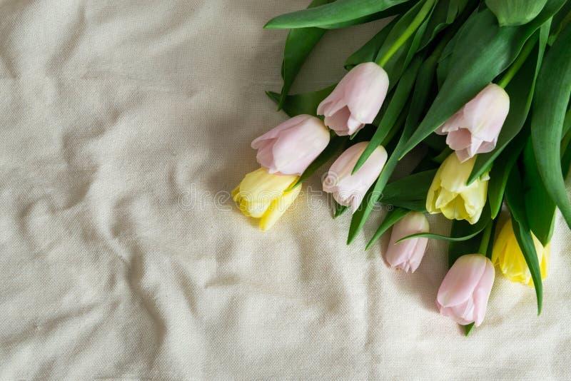 Ramo de tulipanes amarillos rosados en fondo beige de la tela Regalo de la primavera El d?a de madre, d?a de San Valent?n y fondo imagen de archivo libre de regalías