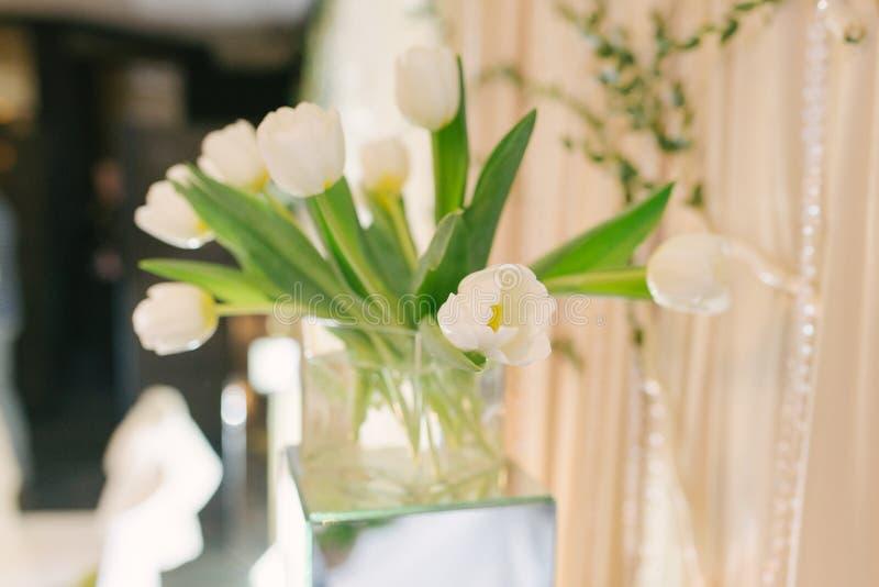 Ramo de tulipanes blancos en un cuadrado de cristal Vahe en la decoración y la decoración de una boda imagen de archivo