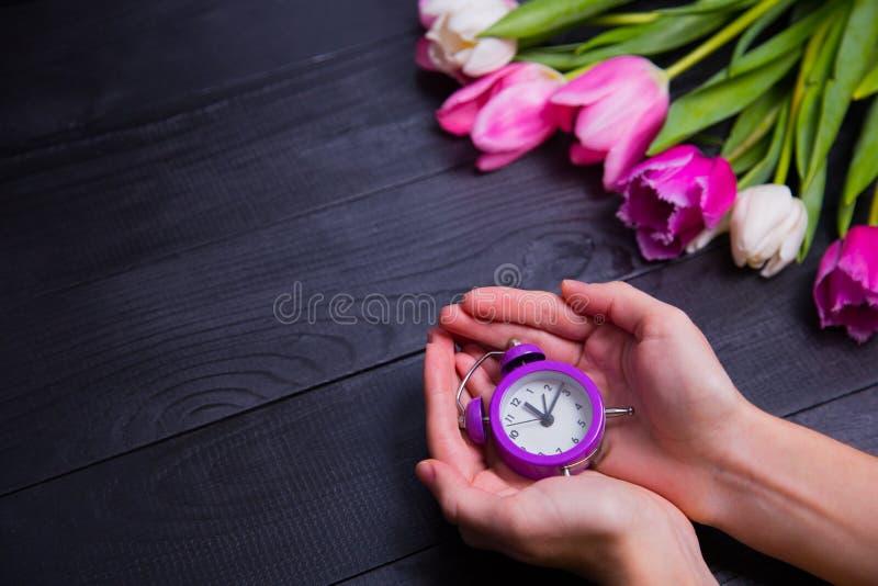 Ramo de tulipanes blandos y de manos rosados que sostienen el reloj púrpura encendido fotos de archivo libres de regalías