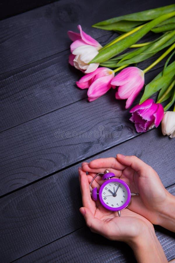 Ramo de tulipanes blandos y de manos rosados que sostienen el reloj púrpura encendido imagenes de archivo