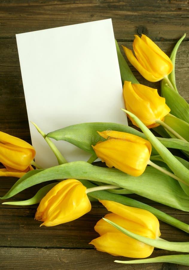 Ramo de tulipanes con la tarjeta en blanco en de madera viejo foto de archivo libre de regalías