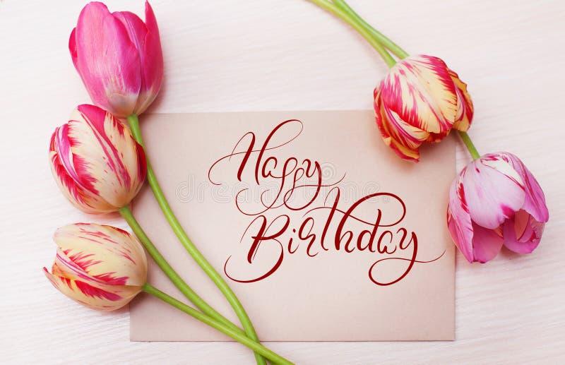 Ramo de tulipanes rojos en el fondo blanco con feliz cumpleaños del texto Letras de la caligrafía foto de archivo