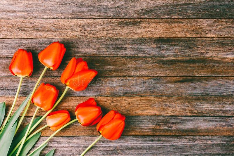 Ramo de tulipanes rojos en fondo retro de madera del grunge con el espacio de la copia foto de archivo libre de regalías