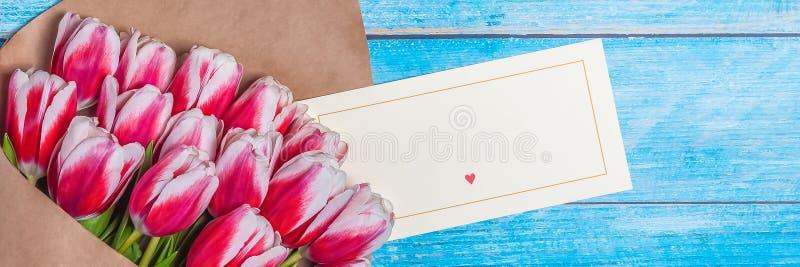 Ramo de tulipanes rojos para el día de las mujeres del día de fiesta y el día de tarjeta del día de San Valentín en el fondo de t imagen de archivo libre de regalías