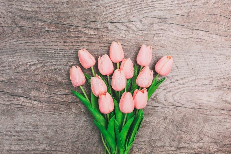 Ramo de tulipanes rosados en fondo de madera foto de archivo libre de regalías