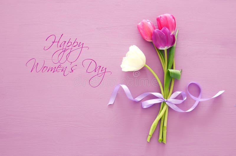 ramo de tulipanes rosados y blancos sobre fondo de madera en colores pastel Visión superior Concepto internacional del día de las foto de archivo