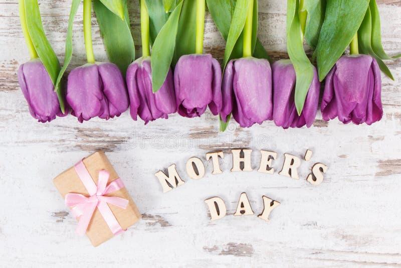 Ramo de tulipanes y de regalo púrpuras para el día de madre en los tableros rústicos blancos foto de archivo