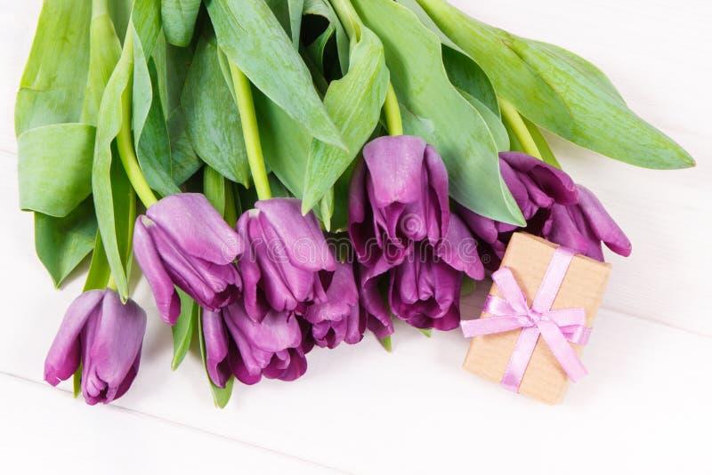 Ramo de tulipanes y de regalo púrpuras para las diversas ocasiones o celebración en los tableros blancos imagen de archivo libre de regalías