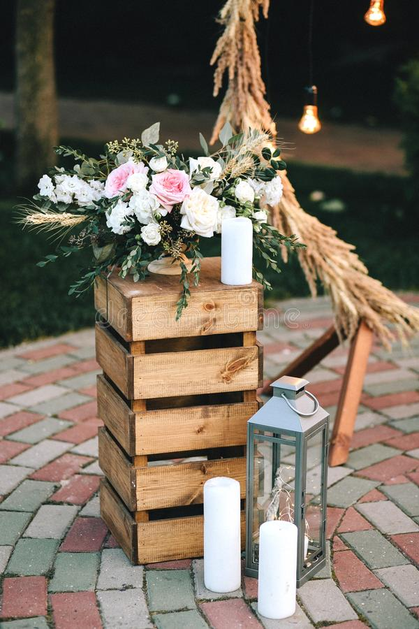 Ramo del pedestal de la caja de madera de flores y de eucalipto cerca de la palmatoria y de las velas blancas Arco de la boda de  imagenes de archivo
