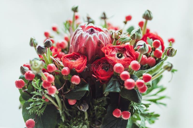 Ramo del Protea y de los ranúnculos en un fondo gris blured imágenes de archivo libres de regalías