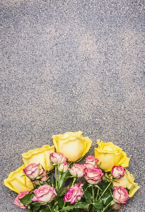 Ramo del regalo de las rosas amarillas y rojas, lugar rústico de la opinión superior del fondo del granito para el texto fotografía de archivo