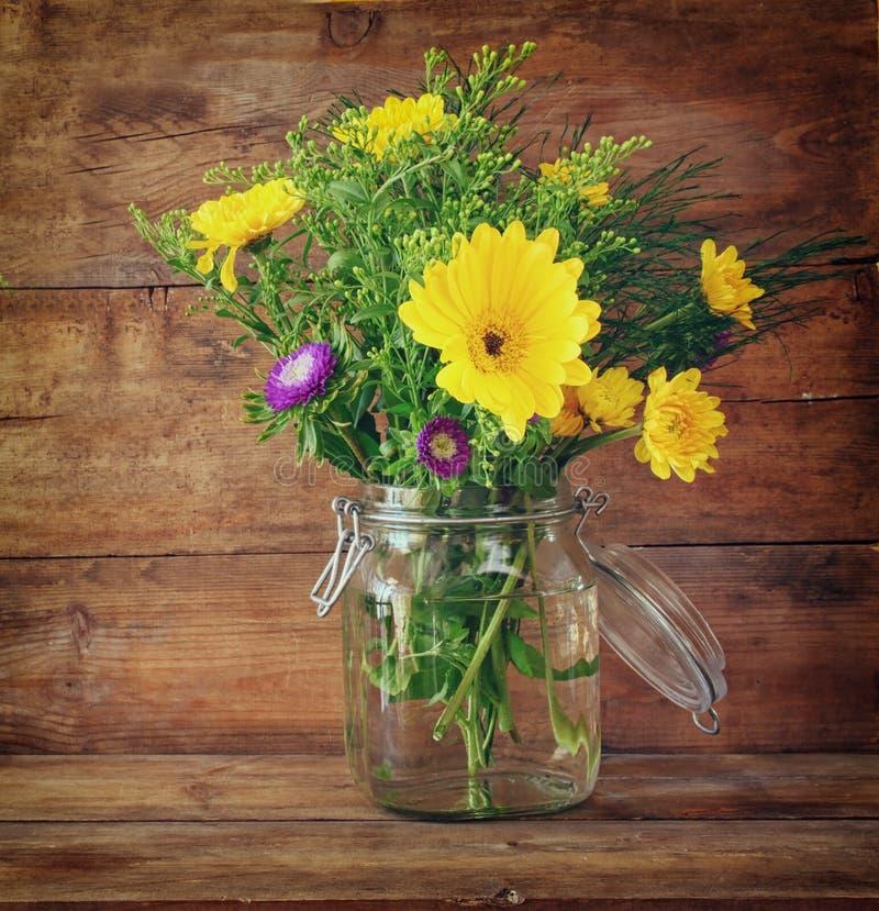 Ramo del verano de flores en la tabla de madera con el fondo de la menta imagen filtrada vintage imágenes de archivo libres de regalías
