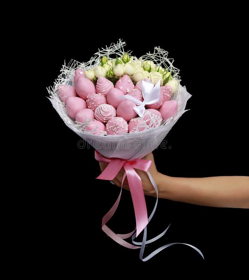 Ramo delicado hermoso que consiste en las fresas en chocolate rosado y rosas blancas en mano femenina en un fondo negro fotos de archivo