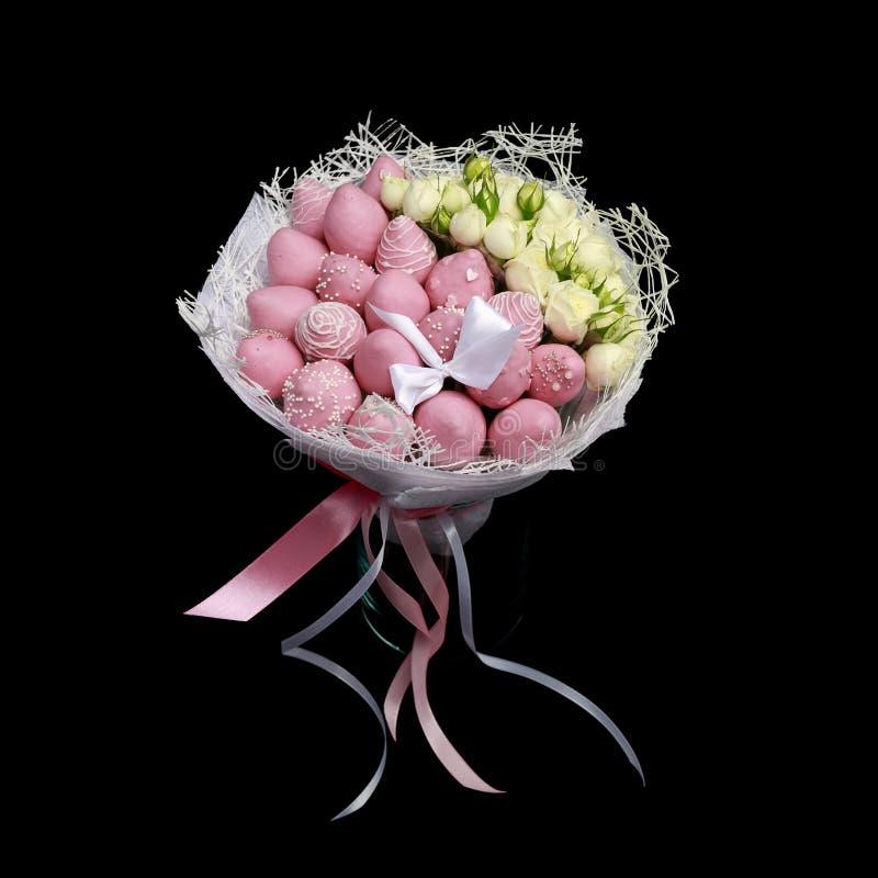 Ramo delicado hermoso que consiste en las fresas en soportes del chocolate rosado y de las rosas blancas en un florero de cristal fotografía de archivo libre de regalías