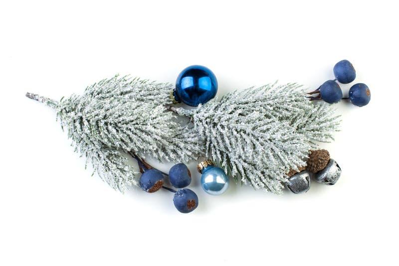 Ramo dell'abete di Natale con le bagattelle d'argento, le bacche blu ed altri ornamenti isolati su bianco immagini stock