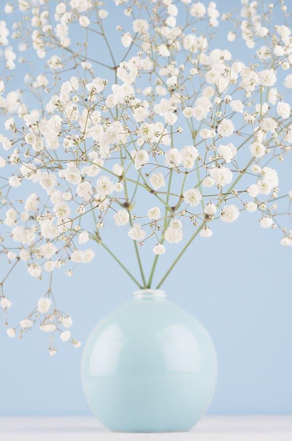 Ramo della primavera con i piccoli fiori bianchi in vaso blu della sfera sulla parete moderna blu-chiaro molle e sulla tavola bia immagine stock libera da diritti