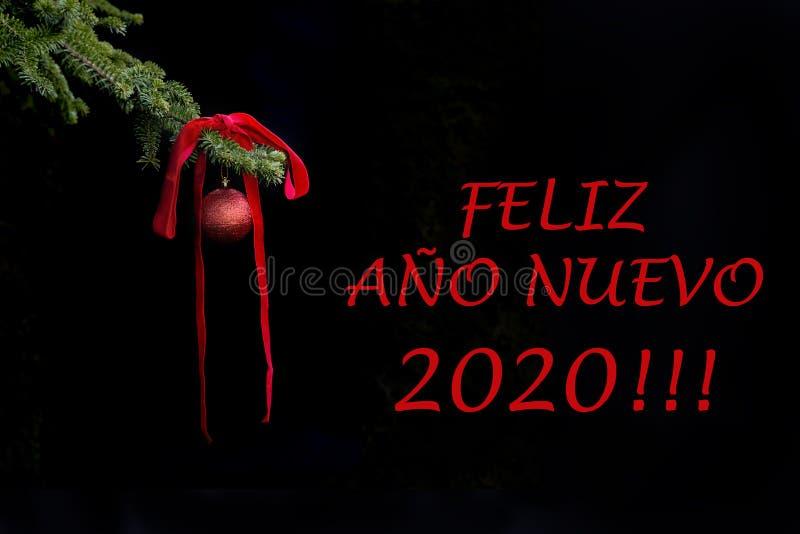 Ramo di albero dell'abete con la palla rossa di scintillio e nastro su fondo scuro effetti Cartolina 2019 di saluti del nuovo ann fotografie stock