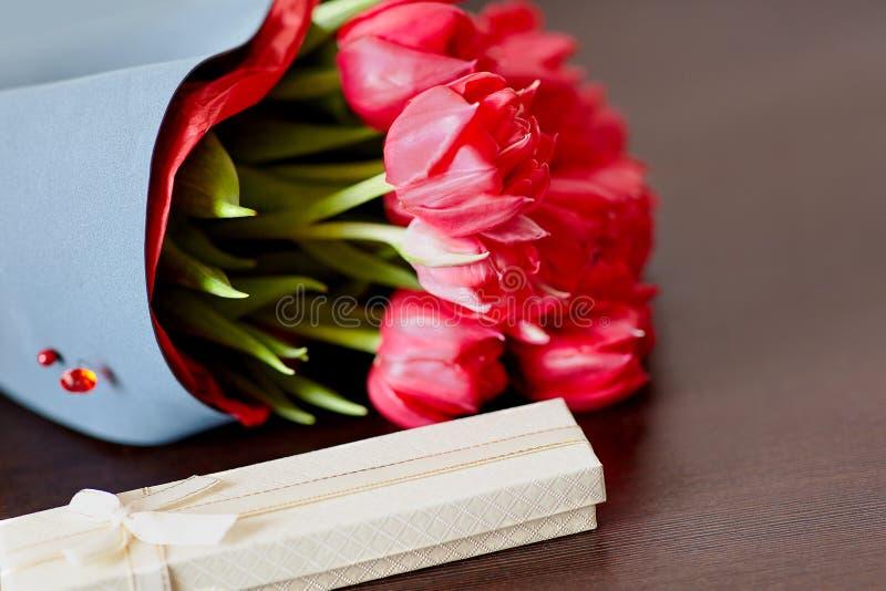 Ramo diseñado de tulipanes rojos frescos con una caja de regalo en fondo verde claro imagen de archivo libre de regalías