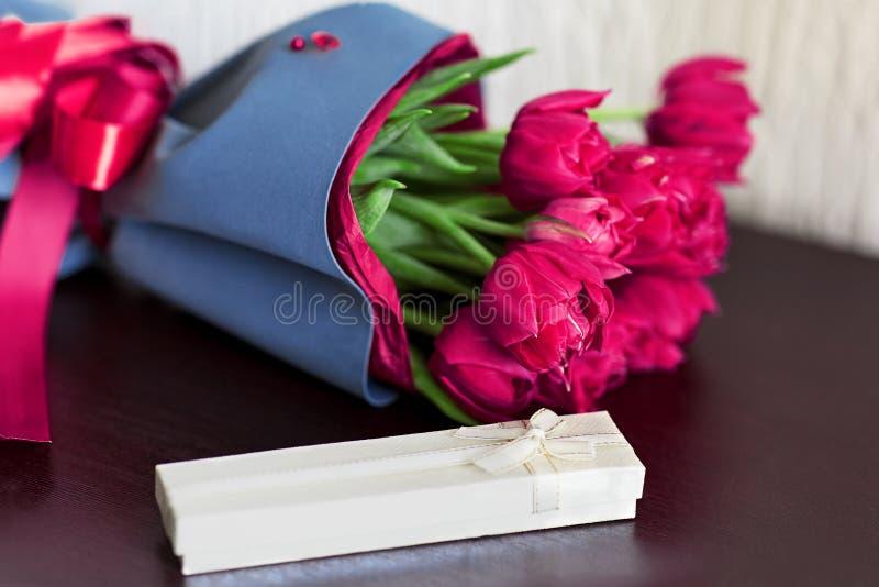 Ramo diseñado de tulipanes rosados del brigh fresco con una caja de regalo en fondo verde claro fotos de archivo libres de regalías