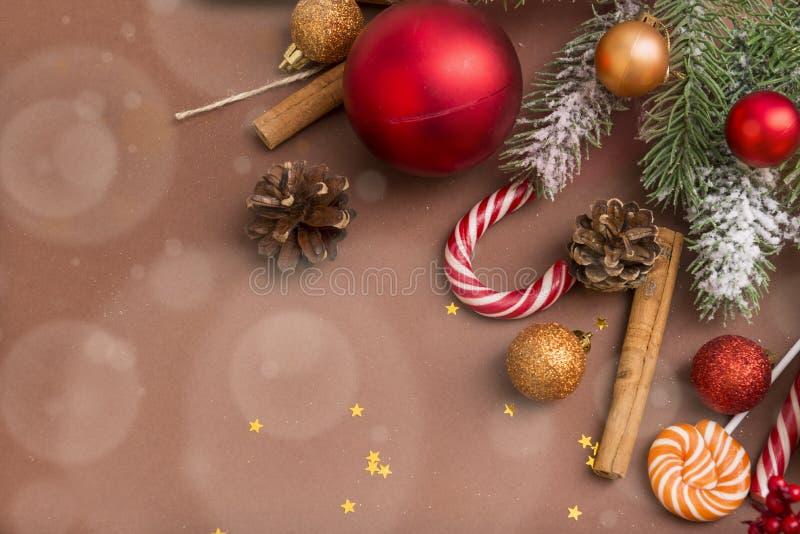 Ramo do abeto, cones de abeto, ouro e bolas vermelhas do Natal, pirulito em um fundo marrom, varas de canela, estrelas imagens de stock