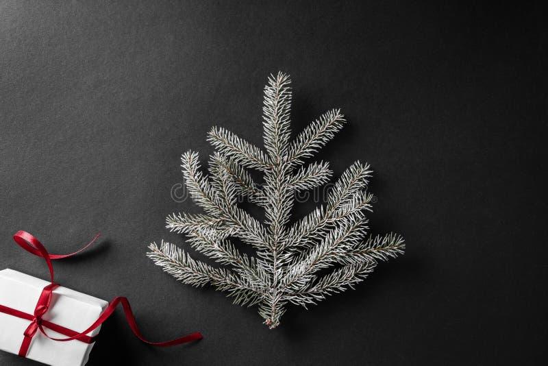 Ramo do abeto do Natal no fundo preto escuro com caixas de presente Tema do Xmas e do ano novo Configuração lisa, vista superior foto de stock royalty free