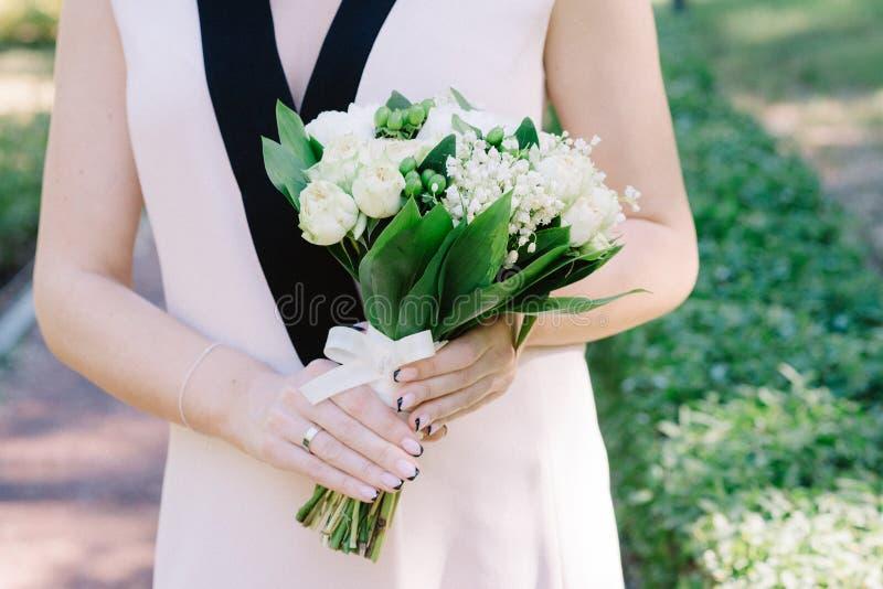 Ramo elegante de la boda del lirio de los valles en las manos de la novia imagenes de archivo
