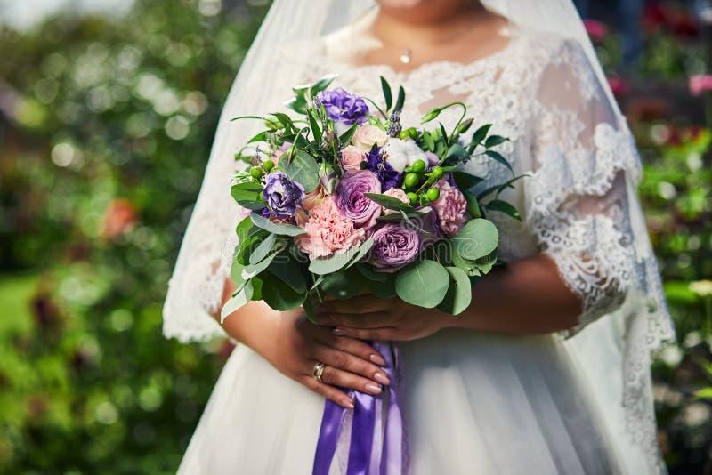 Ramo en las manos de la novia, mujer que consigue lista antes de ceremonia de boda foto de archivo