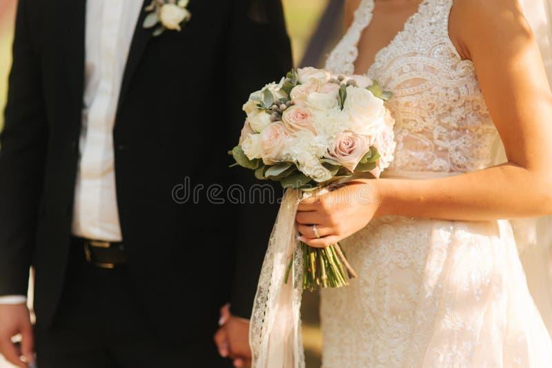 Ramo en manos de las novias Novio con su esposa mediados de celection imagen de archivo libre de regalías