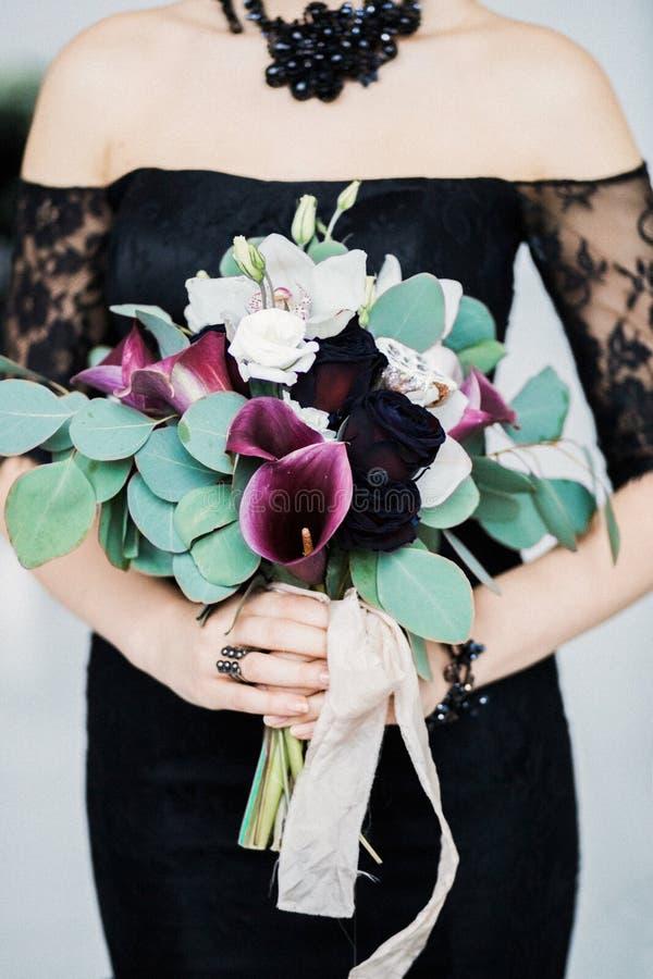 Ramo en manos del ` s de la novia, primer, vestido negro de la boda fotos de archivo libres de regalías