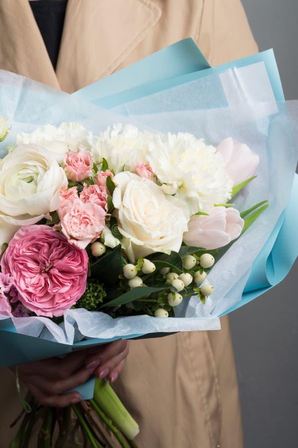 Ramo enorme de flores frescas en una envoltura hermosa en manos femeninas foto de archivo