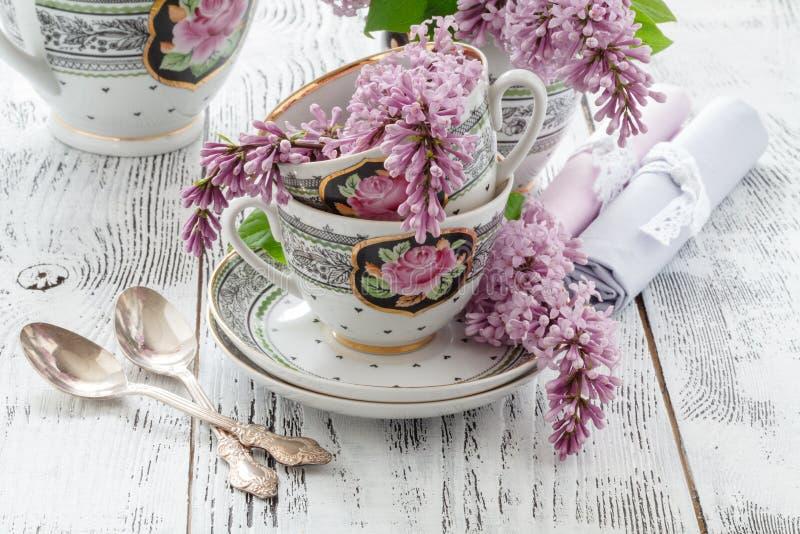 Ramo floreciente del verano de lila y de taza de China con té negro fotografía de archivo libre de regalías