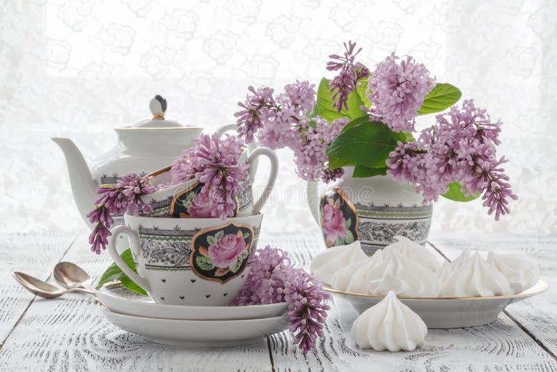 Ramo floreciente del verano de lila y de taza de China con té negro foto de archivo