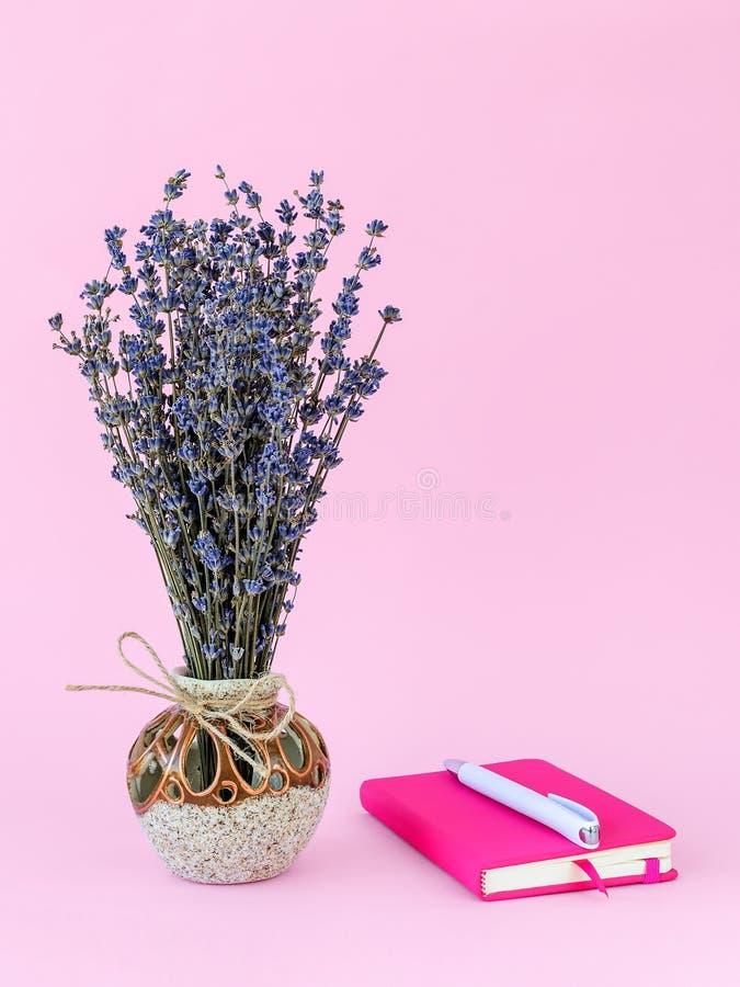 Ramo fragante de lavanda seca con las pequeñas flores púrpuras en un florero de cerámica hermoso y un bolígrafo blanco en el pape imágenes de archivo libres de regalías