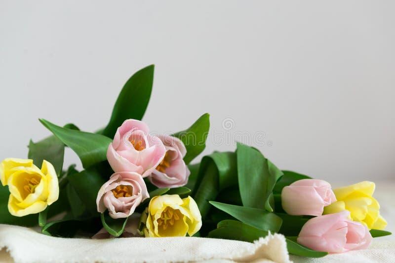 Ramo fresco de rosa y de tulipanes amarillos en fondo ligero Concepto del d?a de fiesta Regalo de la primavera fotografía de archivo libre de regalías