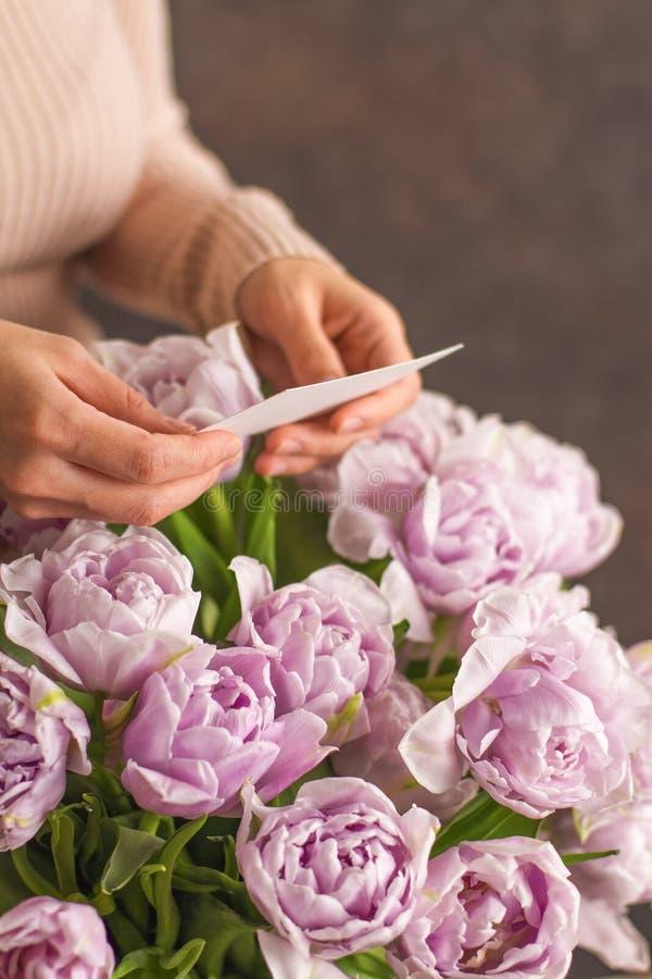 Ramo grande hermoso de flores violetas dobles del tulipán con la tarjeta de felicitación en blanco en un fondo oscuro del rustik  imagen de archivo libre de regalías