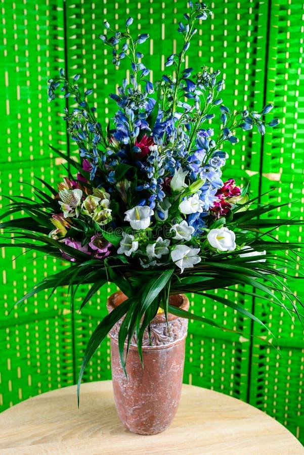 Ramo hermoso con las flores azules de la floración y blancas frescas en vaso imagenes de archivo
