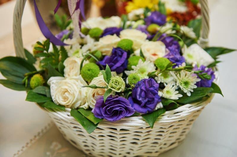 Ramo hermoso de flores blancas y púrpuras en cesta en la tabla de madera fotos de archivo