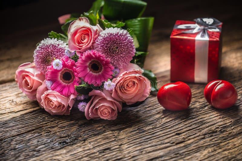Ramo hermoso de flores con el regalo y los corazones rojos en de madera imágenes de archivo libres de regalías