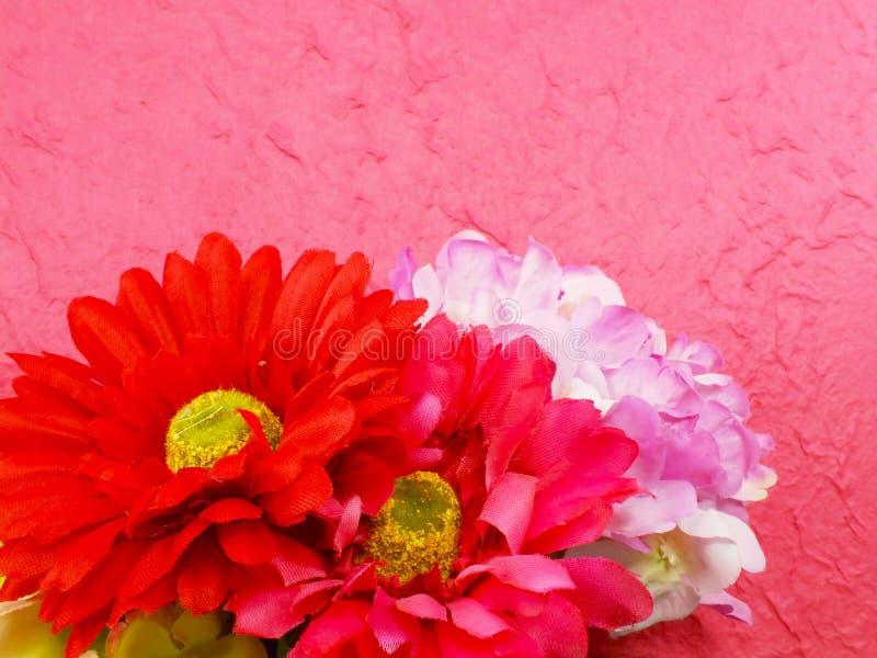 Ramo hermoso de flores falsas en fondo rosado imágenes de archivo libres de regalías