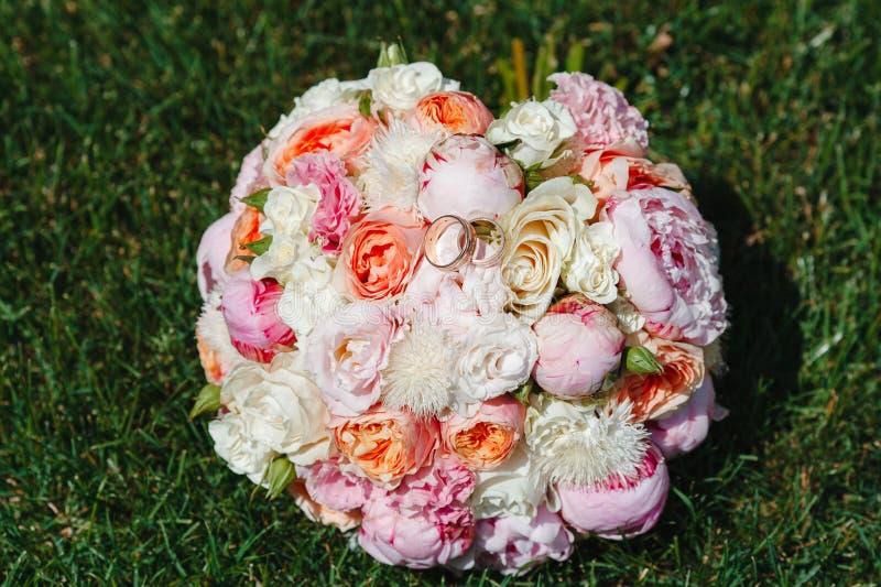 Ramo hermoso de flores que mienten en la hierba verde con los anillos de bodas del oro fotos de archivo libres de regalías