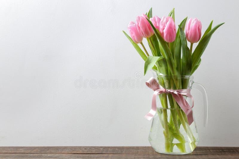 Ramo hermoso de flores de tulipanes rosados en un florero contra la perspectiva de una pared gris Lugar para el texto días de fie foto de archivo