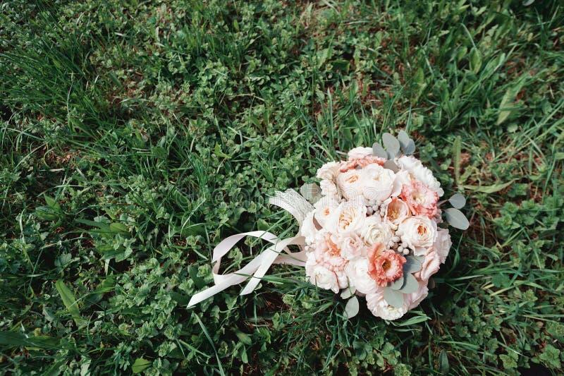 Ramo hermoso de la boda de flores y de cintas en la hierba verde rosas imagen de archivo